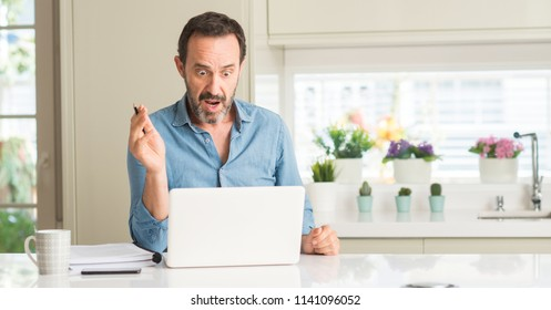Middle age man using laptop at home scared in shock with a surprise face, afraid and excited with fear expression