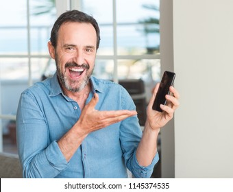 Middle age man using smartphone very happy pointing with hand and finger