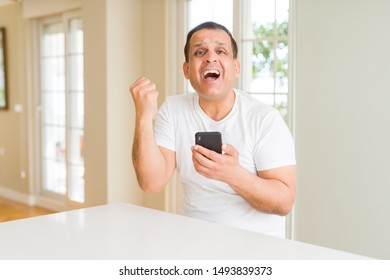 Middle age man using smartphone at home screaming proud and celebrating victory and success very excited, cheering emotion