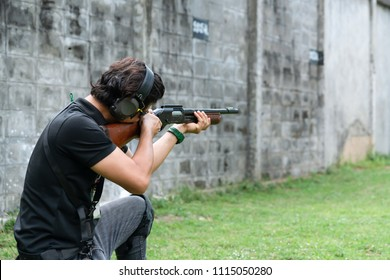 Middle age Man wear Ear plug sitting and aiming shotgun at Target in Shooting Range. Men Practicing Fire Pistol Shooting.