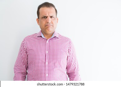 Middle age man wearing business shirt over white wall skeptic and nervous, frowning upset because of problem. Negative person.