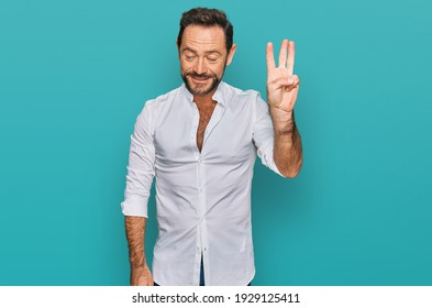 Middle age man wearing casual clothes showing and pointing up with fingers number three while smiling confident and happy.