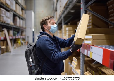 Middle age man wearing protection face mask choosing box in store. Social distancing restrictions and facemask - measures safety while coronavirus pandemic.