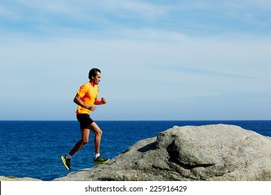 Middle age man at workout outdoors jogging along the sea at sunny day, male jogger in fluorescent t-shirt runs over sea rocks at morning training outdoors