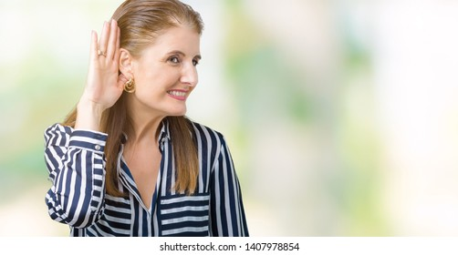 Middle age mature business woman over isolated background smiling with hand over ear listening an hearing to rumor or gossip. Deafness concept.