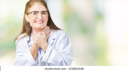 Middle age mature doctor woman wearing medical coat over isolated background shouting and suffocate because painful strangle. Health problem. Asphyxiate and suicide concept.