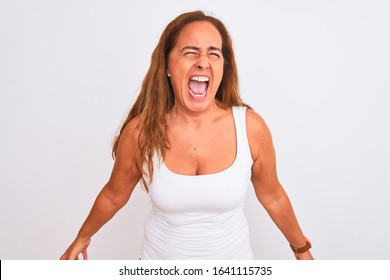 Middle age mature woman standing over white isolated background angry and mad screaming frustrated and furious, shouting with anger. Rage and aggressive concept.