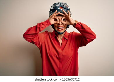 Middle age motorcyclist woman wearing motorcycle helmet over isolated white background doing ok gesture like binoculars sticking tongue out, eyes looking through fingers. Crazy expression.