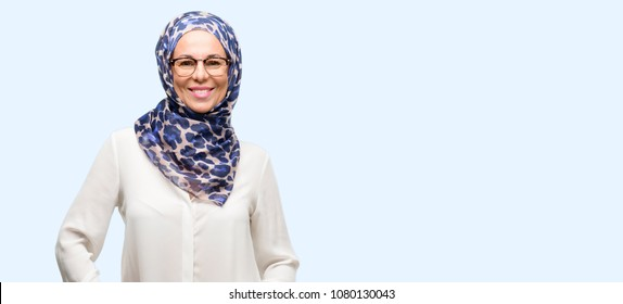 Middle age muslim arab woman wearing hijab confident and happy with a big natural smile laughing isolated blue background