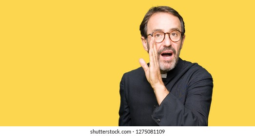 Middle age priest man wearing catholic robe hand on mouth telling secret rumor, whispering malicious talk conversation