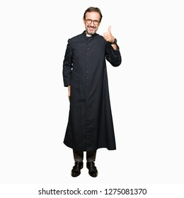Middle age priest man wearing catholic robe doing happy thumbs up gesture with hand. Approving expression looking at the camera showing success.