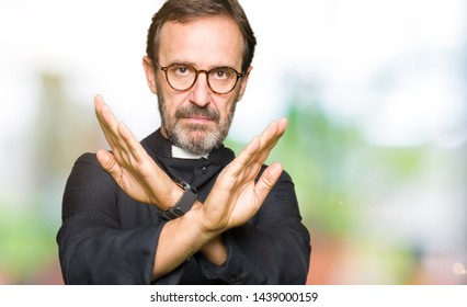 Middle age priest man wearing catholic robe Rejection expression crossing arms and palms doing negative sign, angry face