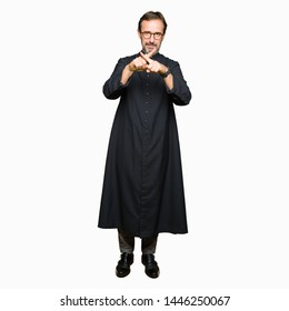 Middle age priest man wearing catholic robe Rejection expression crossing fingers doing negative sign