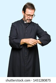 Middle age priest man wearing catholic robe Checking the time on wrist watch, relaxed and confident