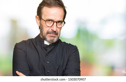Middle age priest man wearing catholic robe skeptic and nervous, disapproving expression on face with crossed arms. Negative person.