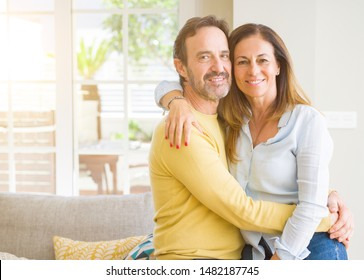 Middle age romantic couple sitting on the sofa at home