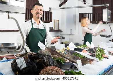 Middle age seller and assistant offering fresh fish in fish store