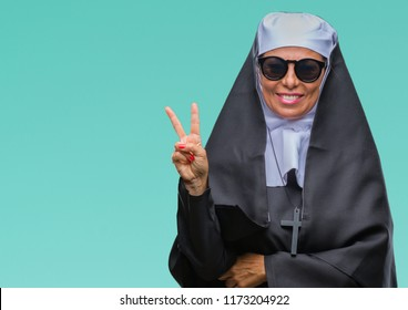 Middle age senior catholic nun woman wearing sunglasses over isolated background smiling with happy face winking at the camera doing victory sign. Number two.