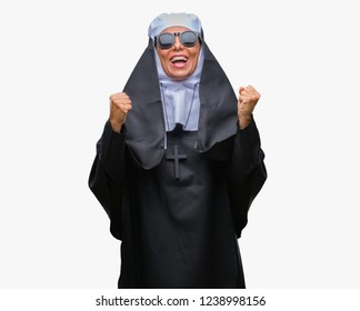 Middle age senior catholic nun woman wearing sunglasses over isolated background celebrating surprised and amazed for success with arms raised and open eyes. Winner concept.