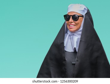 Middle age senior catholic nun woman wearing sunglasses over isolated background looking away to side with smile on face, natural expression. Laughing confident.