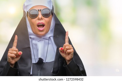 Middle age senior catholic nun woman wearing sunglasses over isolated background amazed and surprised looking up and pointing with fingers and raised arms.