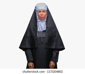 Middle age senior christian catholic nun woman over isolated background with serious expression on face. Simple and natural looking at the camera.