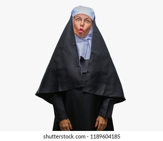 Middle age senior christian catholic nun woman over isolated background making fish face with lips, crazy and comical gesture. Funny expression.