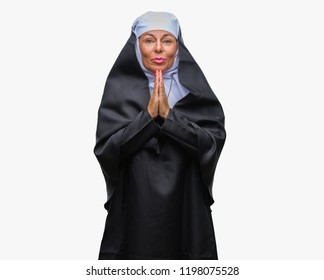 Middle age senior christian catholic nun woman over isolated background praying with hands together asking for forgiveness smiling confident.