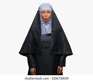 Middle age senior christian catholic nun woman over isolated background afraid and shocked with surprise expression, fear and excited face.