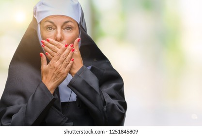 Middle age senior christian catholic nun woman over isolated background shocked covering mouth with hands for mistake. Secret concept.