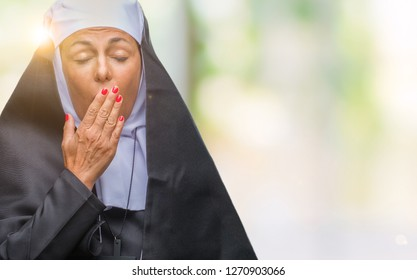 Middle age senior christian catholic nun woman over isolated background bored yawning tired covering mouth with hand. Restless and sleepiness.