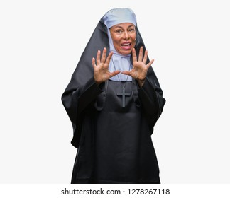 Middle age senior christian catholic nun woman over isolated background afraid and terrified with fear expression stop gesture with hands, shouting in shock. Panic concept.