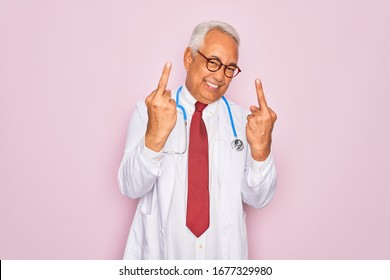 Middle age senior grey-haired doctor man wearing stethoscope and professional medical coat Showing middle finger doing fuck you bad expression, provocation and rude attitude. Screaming excited