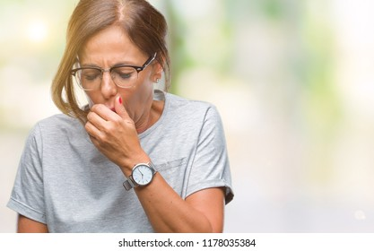 Middle age senior hispanic woman wearing glasses over isolated background feeling unwell and coughing as symptom for cold or bronchitis. Healthcare concept.