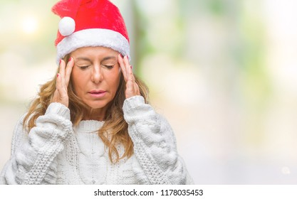 Middle age senior hispanic woman wearing christmas hat over isolated background with hand on head for pain in head because stress. Suffering migraine.