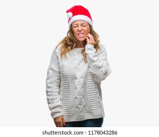 Middle age senior hispanic woman wearing christmas hat over isolated background touching mouth with hand with painful expression because of toothache or dental illness on teeth. Dentist concept.
