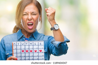 Middle age senior hispanic woman holding menstruation calendar over isolated background annoyed and frustrated shouting with anger