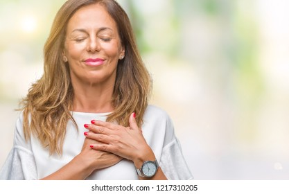 Middle age senior hispanic woman over isolated background smiling with hands on chest with closed eyes and grateful gesture on face. Health concept.