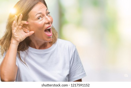 Middle age senior hispanic woman over isolated background smiling with hand over ear listening an hearing to rumor or gossip. Deafness concept.