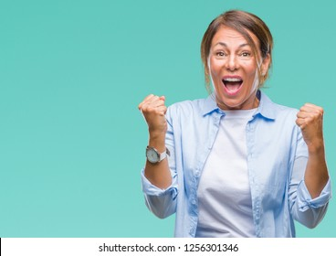 Middle age senior hispanic woman over isolated background celebrating surprised and amazed for success with arms raised and open eyes. Winner concept.