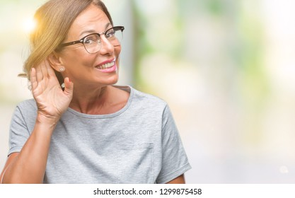 Middle age senior hispanic woman wearing glasses over isolated background smiling with hand over ear listening an hearing to rumor or gossip. Deafness concept.