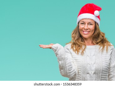Middle age senior hispanic woman wearing christmas hat over isolated background smiling cheerful presenting and pointing with palm of hand looking at the camera.