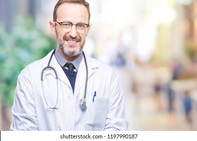 Middle age senior hoary doctor man wearing medical uniform isolated background with a happy and cool smile on face. Lucky person.