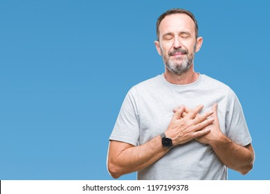 Middle age senior hoary man over isolated background smiling with hands on chest with closed eyes and grateful gesture on face. Health concept.