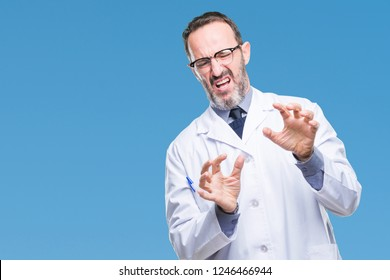Middle age senior hoary professional man wearing white coat over isolated background disgusted expression, displeased and fearful doing disgust face because aversion reaction. With hands raised