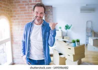 Middle age senior man moving to a new house packing cardboard boxes smiling with happy face looking and pointing to the side with thumb up.