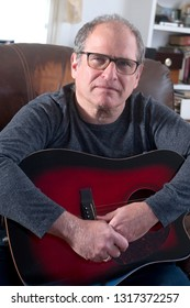middle age senior man musician playing acoustic guitar happy and smiling