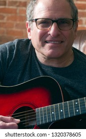 middle age senior man musician playing acoustic guitar  and performing entertainment while smiling and happy
