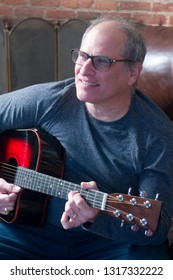 middle age senior man playing acoustic guitar happy and smiling
