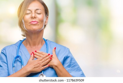 Middle age senior nurse doctor woman over isolated background smiling with hands on chest with closed eyes and grateful gesture on face. Health concept.